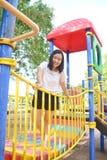 Mädchen, das am Spielplatz spielt stockfotografie