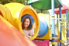 Mädchen, das am Spielplatz spielt stockbild