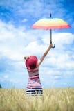 Mädchen, das steigenden Regenschirm und Stellung des roten Hutes trägt Lizenzfreie Stockfotografie