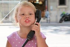 Mädchen, das am Straßentelefon spricht Lizenzfreie Stockfotografie