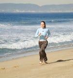 Mädchen, das am Strand läuft Stockfoto