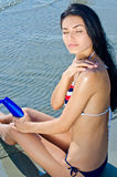 Mädchen, das Suntanlotion anwendet Stockbilder