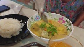 Mädchen, das Suppe im Löffel aufhebt Isst Suppe mit dem Grün Platte des Reises stock video