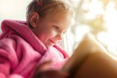 Mädchen, das Tablette am Fenster verwendet Stockbild