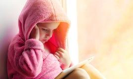 Mädchen, das Tablette am Fenster verwendet Lizenzfreies Stockfoto