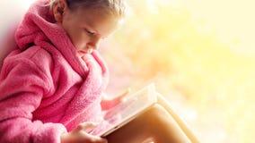 Mädchen, das Tablette am Fenster verwendet Lizenzfreie Stockbilder