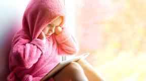 Mädchen, das Tablette am Fenster verwendet Lizenzfreie Stockfotos