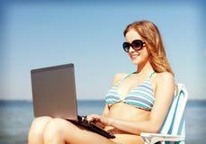 Mädchen, das Tabletten-PC auf dem Strand betrachtet Stockfotos
