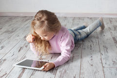 Mädchen, das Tabletten-PC spielt lizenzfreies stockfoto