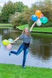 Mädchen, das in Teich mit farbigen Ballonen steht Lizenzfreie Stockfotos
