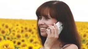Mädchen, das am Telefon auf dem Gebiet von Sonnenblumen, Sommerausflug der Landschaft spricht stock footage