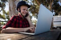 Mädchen, das am Telefon bei der Anwendung des Laptops spricht stockbild