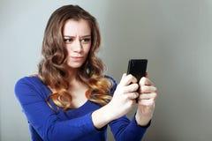 Mädchen, das Telefon betrachtet Lizenzfreies Stockbild