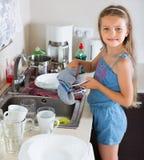 Mädchen, das Teller an der Küche tut Lizenzfreies Stockfoto