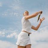 Mädchen, das Tennis auf Hintergrund des Himmels spielt Stockfoto
