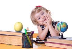 Mädchen, das am Tisch mit Büchern und Kugel sitzt Lizenzfreie Stockfotos