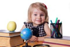 Mädchen, das am Tisch mit Büchern und Kugel sitzt Lizenzfreie Stockfotografie