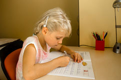Mädchen, das am Tisch studiert Lizenzfreie Stockbilder