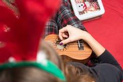Mädchen, das Ukulele für Weihnachten spielt stockfotos