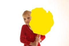 Mädchen, das unbelegtes gelbes Zeichen anhält Lizenzfreie Stockbilder