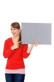 Mädchen, das unbelegtes Plakat anhält Lizenzfreies Stockbild