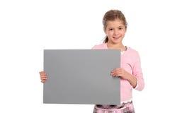 Mädchen, das unbelegtes Zeichen anhält Lizenzfreie Stockfotografie