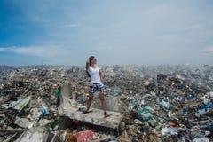 Mädchen, das unter Bergen des Abfalls an der Müllkippe aufwirft Lizenzfreies Stockfoto