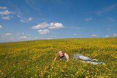Mädchen, das unter Blumen sich entspannt stockfotos