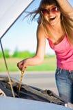 Mädchen, das unter dem Auto schaut Stockbilder