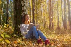 Mädchen, das unter einem Baum mit einem Buch sitzt lizenzfreies stockbild