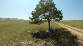 Mädchen, das unter einem Baum, stillstehend im Schatten sitzt und schreiben etwas in ein Notizbuch stock video