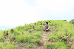 Mädchen, das unter Steinstapeln auf Padar-Insel meditiert Stockbilder