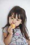 Mädchen, das Vanillepuddingkuchen isst Lizenzfreie Stockfotografie