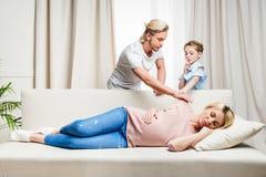 Mädchen, das Vater vom Aufwachen der schwangeren Frau dieses Schlafen auf Sofa stoppt lizenzfreie stockfotografie