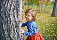 Mädchen, das Verstecken im Park spielt Lizenzfreies Stockbild