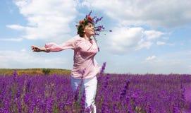 Mädchen, das in violette Blumen läuft Stockfotos