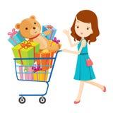 Mädchen, das voll Warenkorb von Geschenken drückt Lizenzfreie Stockfotografie