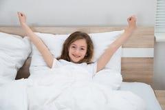 Mädchen, das vom Bett aufwacht stockbild