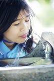Mädchen, das vom Brunnen trinkt Stockfotografie