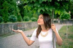 Mädchen, das vom Regen unter einem Baum sich versteckt Stockfoto