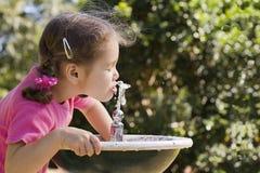 Mädchen, das vom Wasserbrunnen trinkt Lizenzfreie Stockbilder