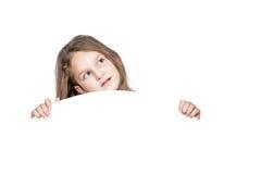 Mädchen, das von hinten eine runde weiße Platte lugt Stockfoto