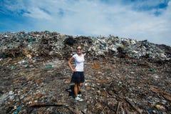 Mädchen, das vor Abfallberg an der Müllkippe steht Stockfotografie