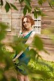 Mädchen, das vor einem Holzhaus im Dorf aufwirft Stockfotos