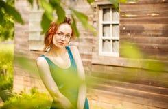 Mädchen, das vor einem Holzhaus im Dorf aufwirft Stockfoto