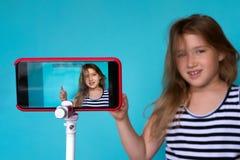 Mädchen, das vor Telefonkamera für selfie aufwirft stockfotografie