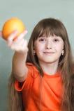 Mädchen, das vorwärts Orange ausgestreckten Arm gibt Stockfotos