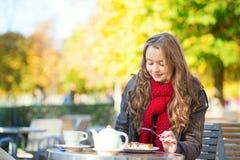 Mädchen, das Waffeln in einem Pariser Café isst Stockbild