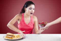 Mädchen, das Wahl zwischen Burger und Erdbeere trifft Stockbilder