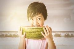 Mädchen, das Wassermelone auf dem Strand isst Stockbilder